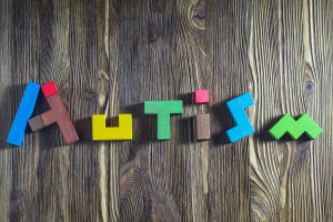 Autism awareness month. Word Autism built of wooden puzzles on a wooden background. Concept of autism word.