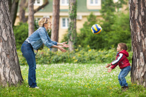 developing hand-eye coordination in children. mother and son throwing ball in park.