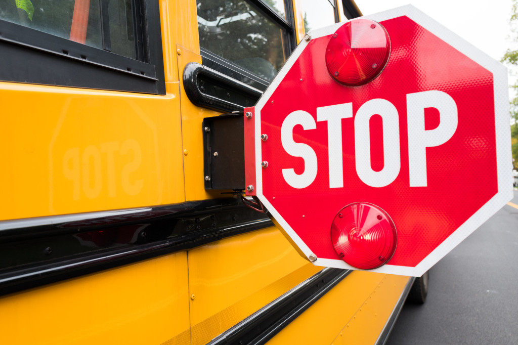 close up of a school bus stop sign on the side of a bus