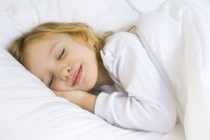Little blond girl wearing white blouse in white bedclothes