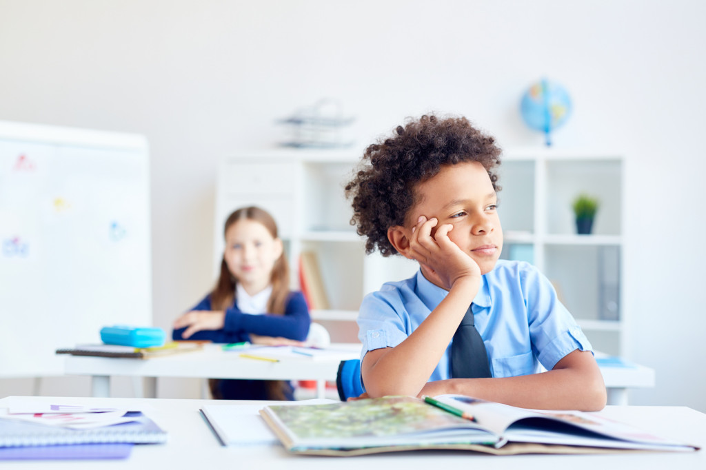 How to support a child who is a gifted underachiever. Child day dreaming in a classroom.
