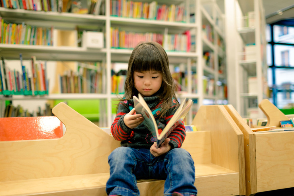 little girl in a library reading a book