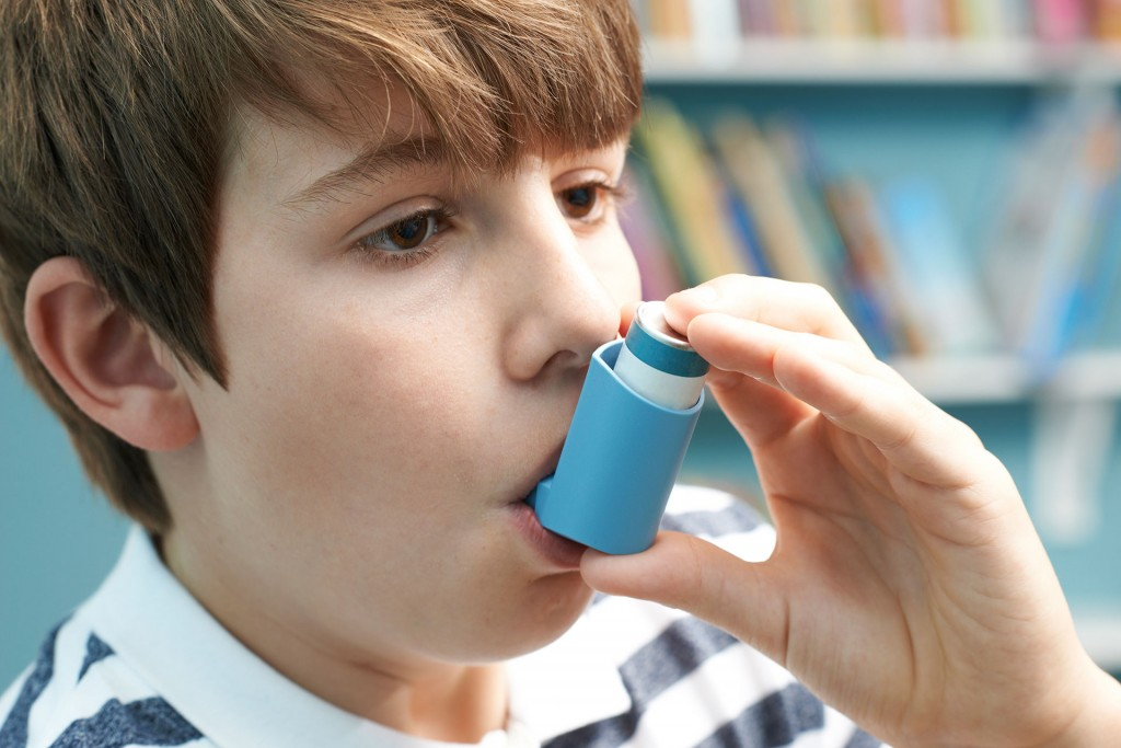 Young boy using inhaler at school during asthma attack