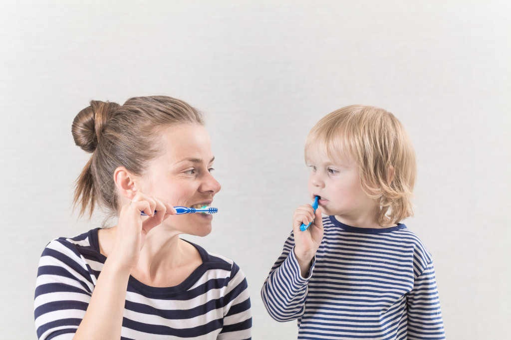 young child learns how to brush his teeth with his mother