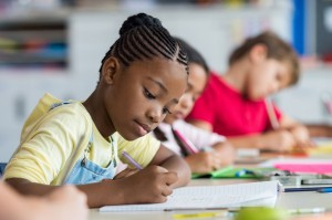 Girl writing in classroom among other students