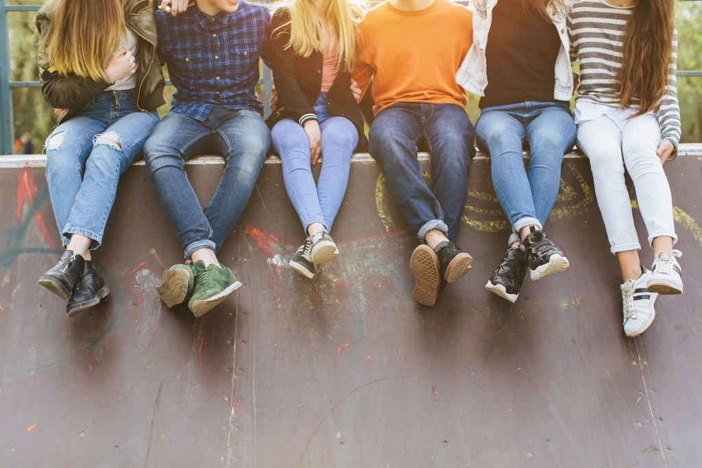teens sitting together on a wall